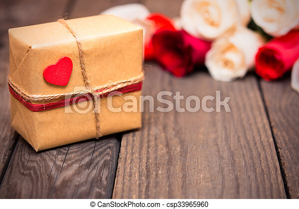Gift box with blured red and white roses on a dark wooden background. Women\' s day, Valentines Day, Mothers day. Copy space, selective focus. Natural optical blur, toned