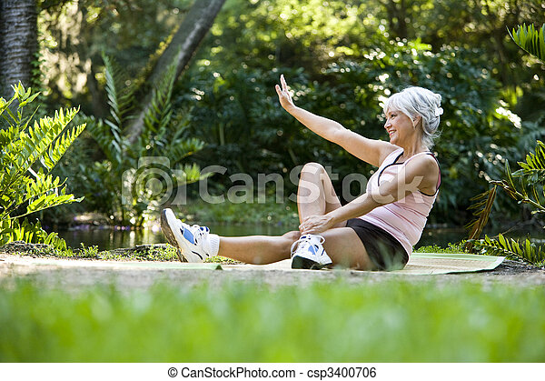 Woman on mat doing stretching exercises outdoors - csp3400706