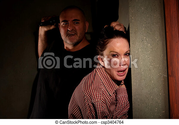 Frightened woman in hallway with menacing man - csp3404764