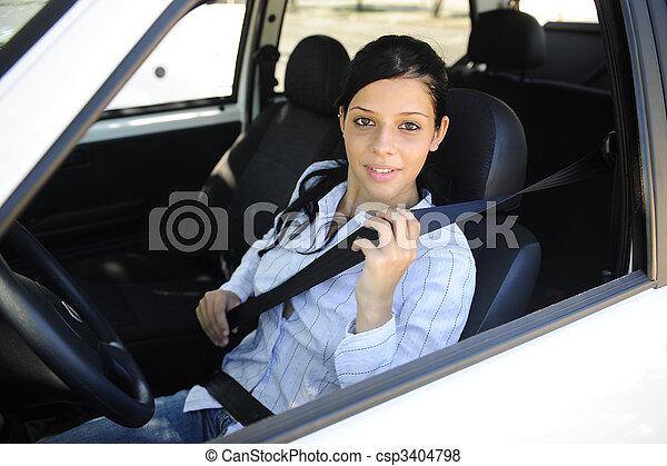 safety: female driver fastening seat belt - csp3404798
