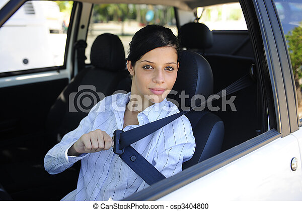 safety: female driver fastening seat belt - csp3404800