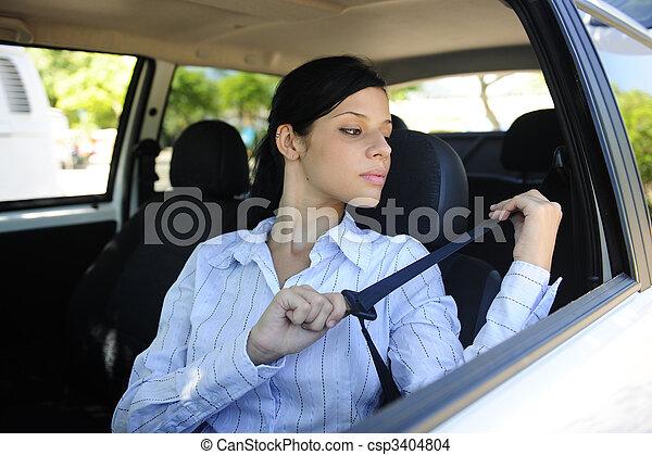 safety: female driver fastening seat belt - csp3404804