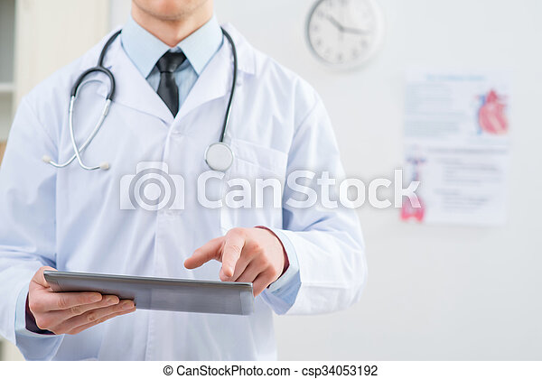 Stay in touch with time. Close p of tablet in hands of professional pleasant doctor holding it while going to work