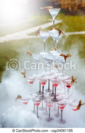 Pyramid of Champagne Glasses with Dry Ice Vapor Ready for Cocktails. Wedding Reception. Selective Focus.