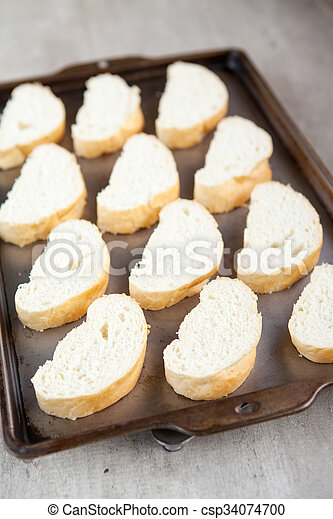 Slices of french bread loaf on baking tray - csp34074700