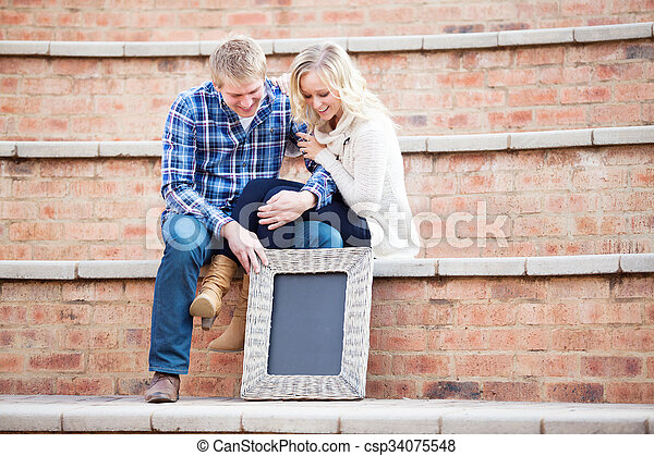 Happy young adult couple looking down at your text, focus on sign - csp34075548