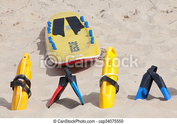 Lifesaving equipment lying on the beach sand - csp34075550