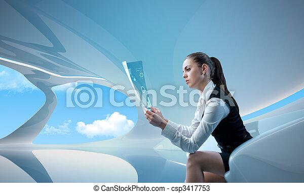 Sexy businesswoman examining future digital report / newspaper - csp3417753