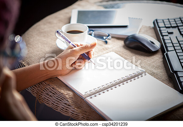 people taking mobile phone and  top table working by writing on white empty paper page with left hand  - csp34201239