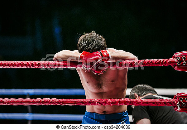 mixed martial arts fighter (MMA) stands in corner ring. lost fight. defeat of an opponent
