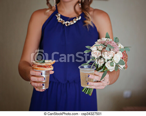 Bridesmaid holding a bouquet for the bride, a sandwich, glasses with champagne. Best Bridesmaids with food and champagne