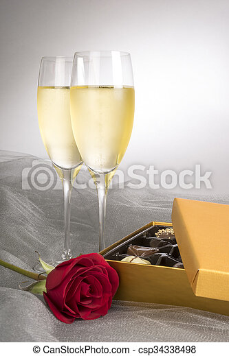 Two Glasses of Champagne with Red Rose and Gourmet Chocolates