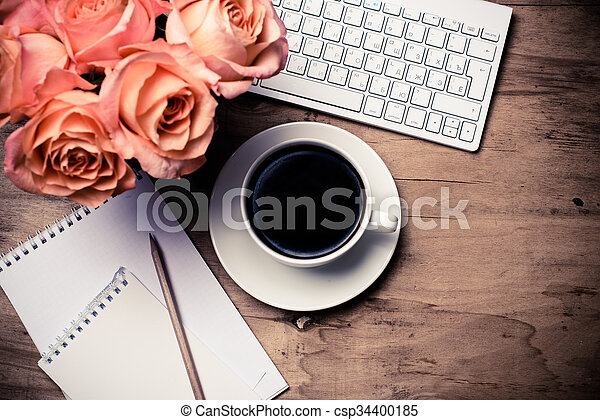 Vintage hipster style office table decor with fresh flowers, computer keyboard and smart phone. Woman\'s modern workspace, interior details, top view.