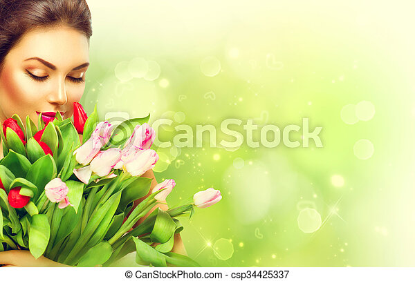 Beautiful girl with a bouquet of colorful tulip flowers