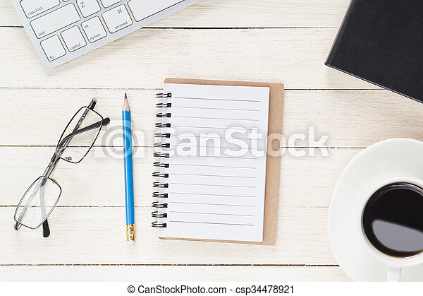 Office workspace with keyboard notepad coffee of cup and smartphone on wood table.