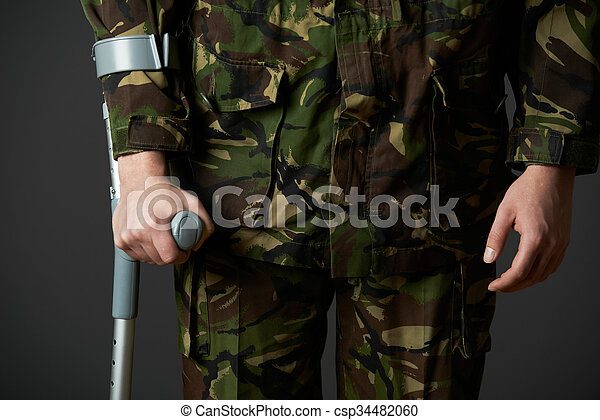 Studio Shot Of Wounded Soldier Using Crutch