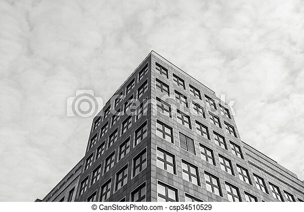 Low angle view of old warehouse loft building under fluffy white clouds in black and white