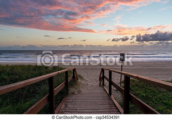 Sunrise ocean beach. Sea beach wooden walkway, path entrance. Sandy ocean beach on sunrise, sunset