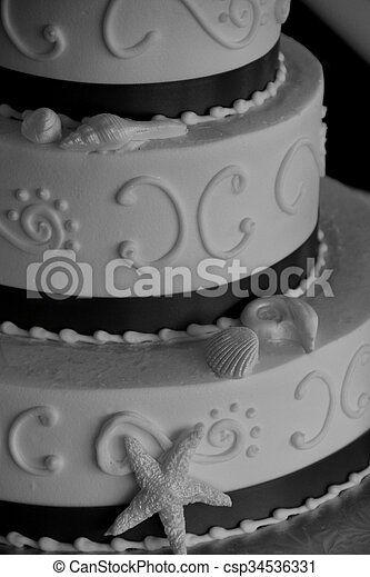 Pretty image of beach themed wedding cake, with ribbon and seashells for decoration.