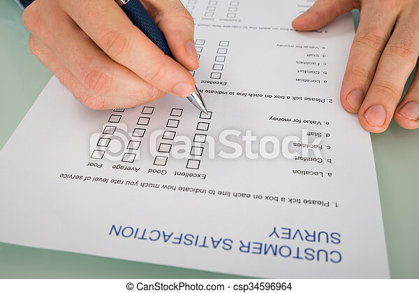 Close-up Of Person Hand Filling Customer Satisfaction Form