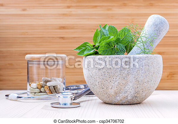 Fresh herbal leaves basil , sage , mint , holy basil , fennel and capsule of herbal medicine alternative health care with stethoscope setup on wooden background.