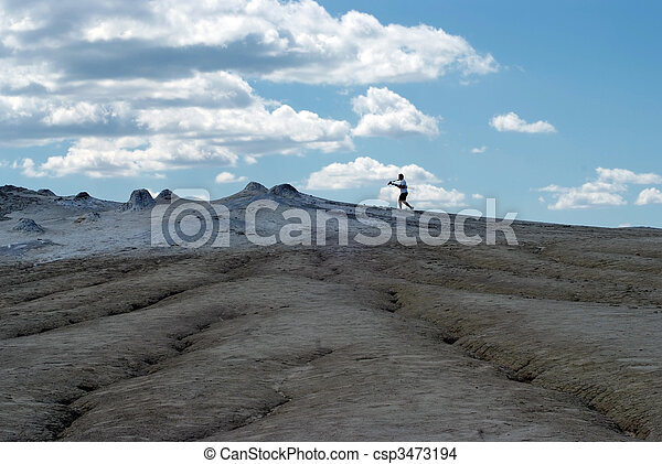 Photographer on arid landscape and blue sky - csp3473194