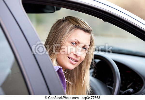 Attractive young female driver sitting in her car - csp3477668