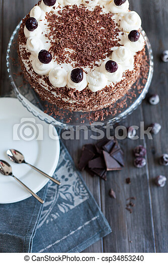 Black forest cake decorated with whipped cream, cherries and with chocolate chips on a dark wooden background.
