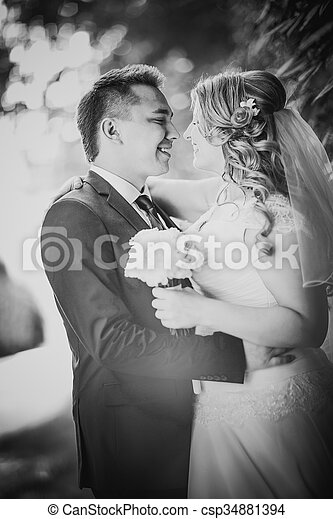 Black white photography happy couple bride and groom embracing they stand on background nature close-up