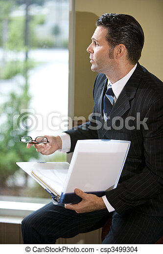 Contemplative businessman looking out office window - csp3499304