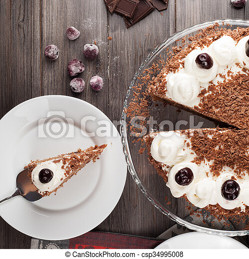Black forest cake decorated with whipped cream, cherries and with chocolate chips on a dark wooden background. Top view.