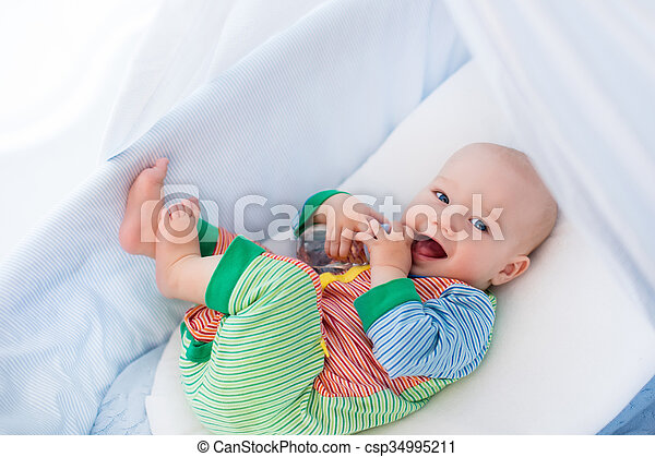 Funny baby in colorful pajamas with bottle drinking water or milk in white crib with canopy. Healthy nutrition for kids. Nursery interior and bedding for infant. Children drink formula in bed.