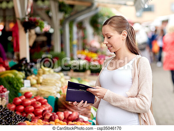 sale, shopping, pregnancy and people concept - happy pregnant woman with wallet buying food at street market
