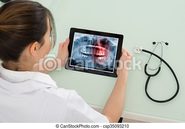 Young Female Doctor Looking At Dental X-ray On Digital Tablet In Clinic