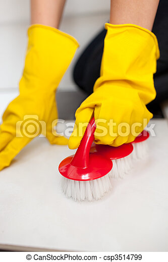 Close-up of a woman cleaning a bathroom\'s floor with a yellow rubber glove