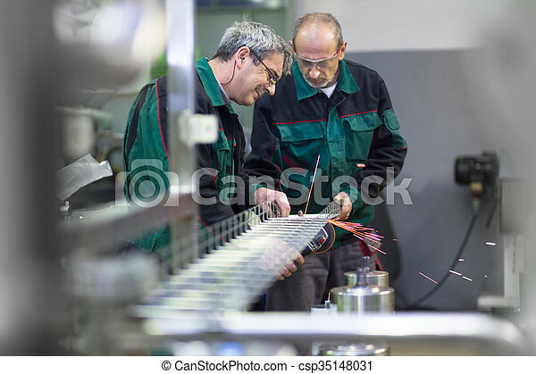 Industrial workers in manufacturing plant building steel structure. Industrial background, industry.