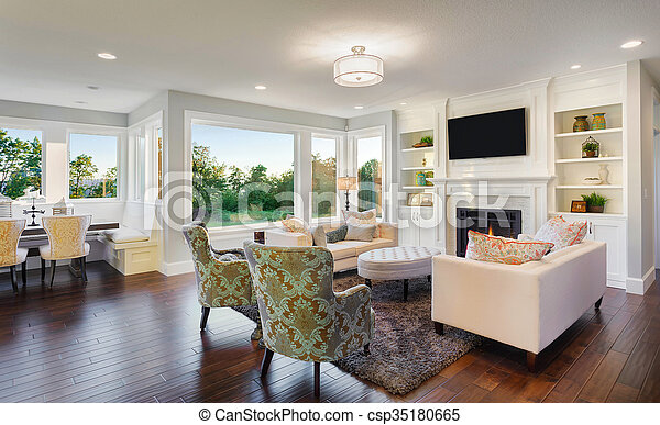 beautiful living room in newly constructed luxury home with hardwood floors, tv, fireplace, couches, and upscale furnishings
