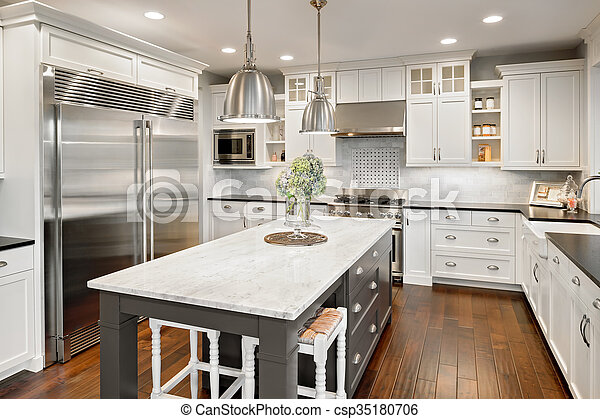 Beautiful Kitchen in Luxury Home with Island and Stainless Steel Refrigerator
