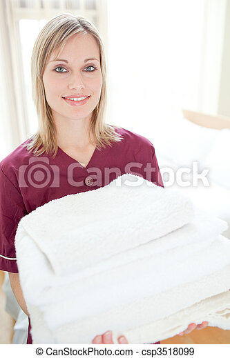 Positive cleaning lady holding towels
