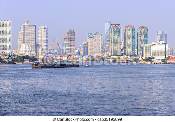 Boat pulled by a tugboat cargo carry the product at the Chaophaya river in Bangkok Thailand.