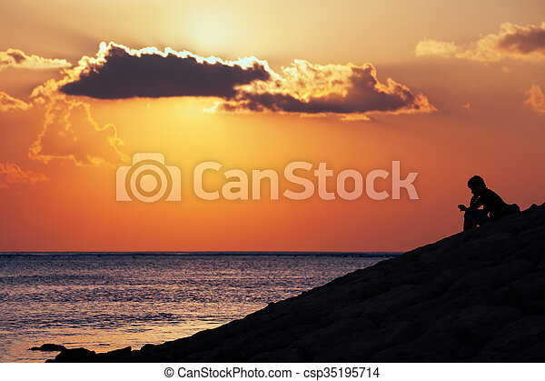 Black silhouette of thinking man sitting alone on the sea beach reading message on mobile phone on sunset sky background. Lifestyle, single people emotions, family conflicts and problem concepts.