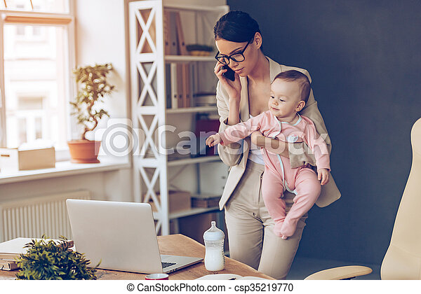 It is not easy to be a working mom! Young beautiful businesswoman talking on mobile phone and looking at laptop while standing with her baby girl at her working place