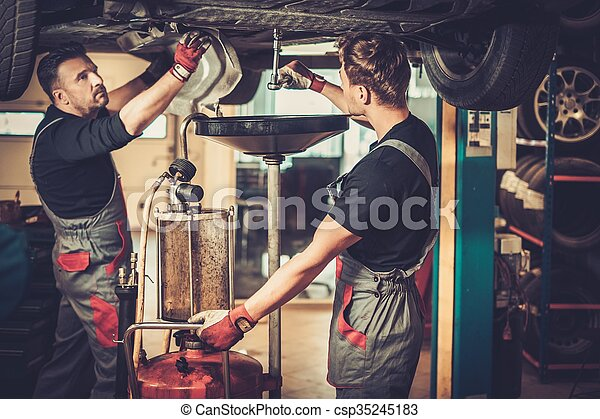 Profecional car mechanic changing motor oil in automobile engine at maintenance repair service station in a car workshop.