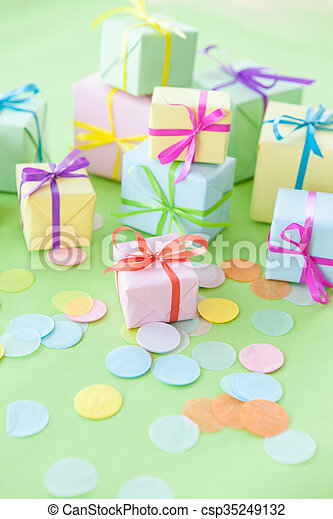 Colorful little gift boxes and confetti on green