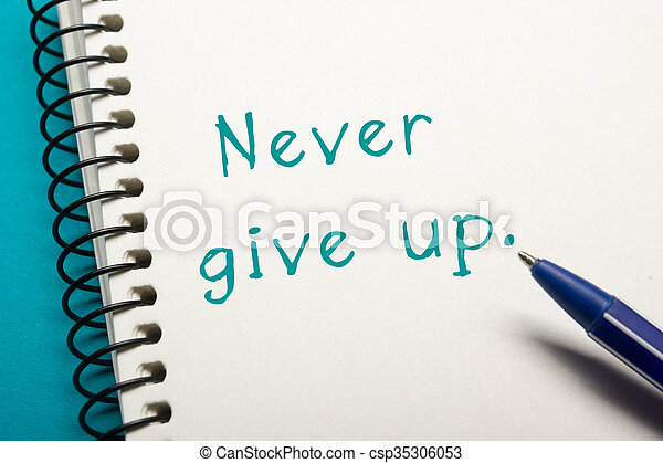 Never give up message - Office table top view. Notepad with text and pen .