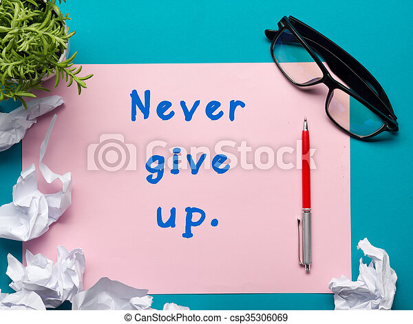 Never give up message - Office desk table with supplies top view. crumled paper, pen, glasses and flower