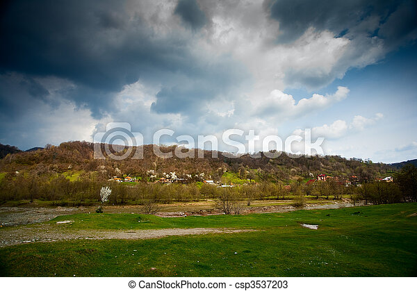 Spring scenery with meadow and cloudy sky - csp3537203
