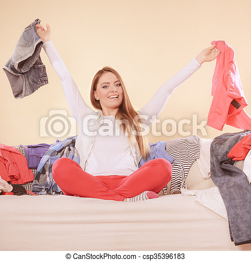 Happy woman sitting on sofa couch in messy living room holding clothes. Young girl surrounded by many stack of clothing. Disorder and mess at home.