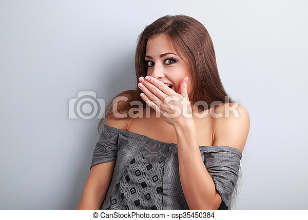Surprise makeup woman cover mouth the hand and looking with big eyes on blue background
