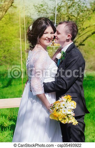 Young bride and groom in the park. Groom and bride in a white dress in the spring garden
